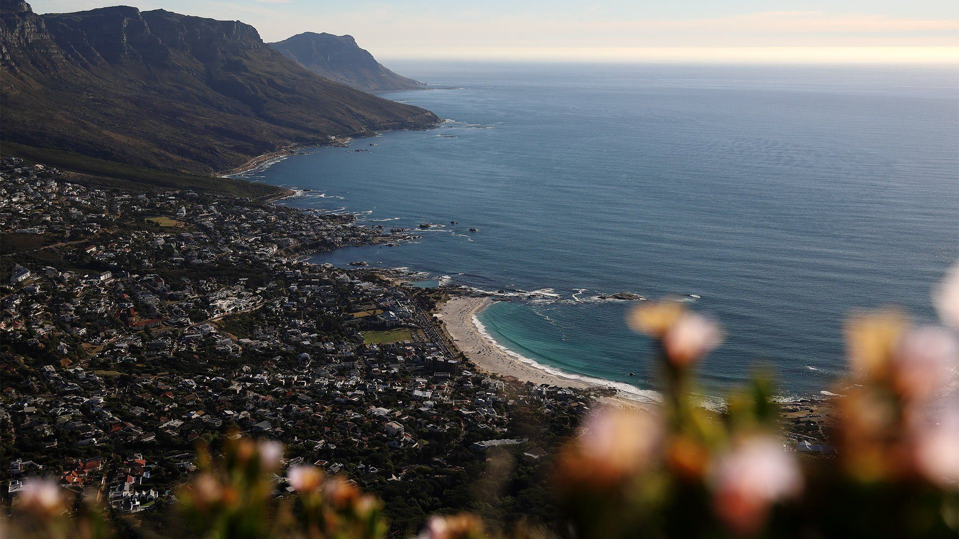 A coastal village in South Africa viewed from a high vantage point, with hills in the distance and the sea stretching to the horizon.